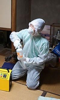 遺品整理の際に行う消毒作業中のスタッフ。
