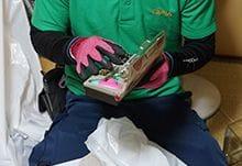 遺品整理の際、裁縫道具を使う男性スタッフ。